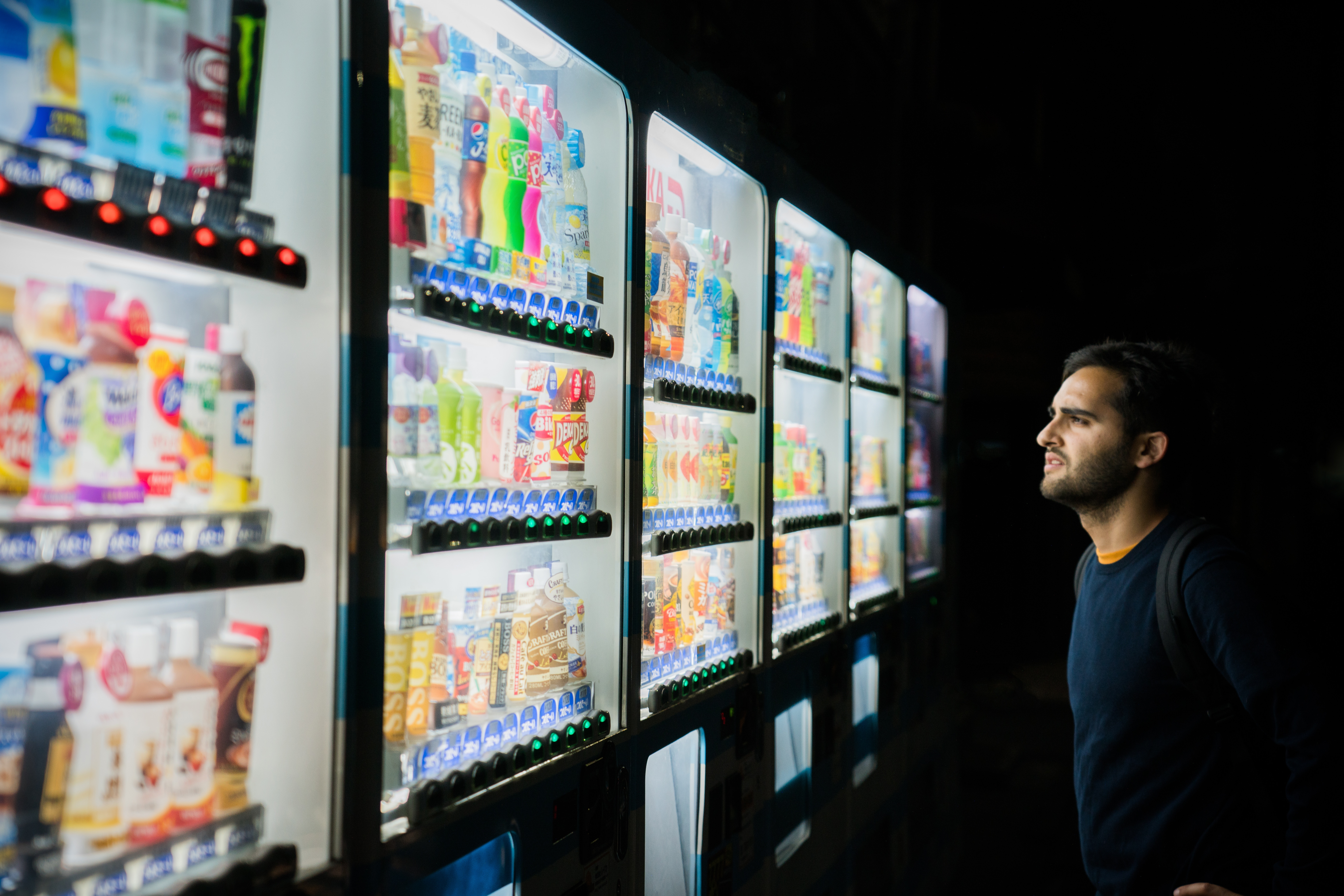 A man in a dark room looking at one of 6 lit up vending machines